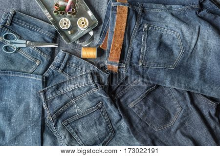 Top View of Jeans and Sewing Tools with on Blue Fabric Background