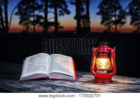 Kerosene lamp and book on a wooden table at night.