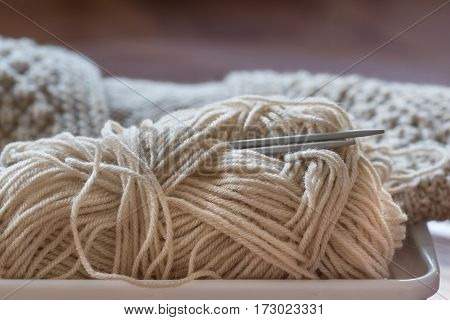 Knitting needles and yarn on wooden background.
