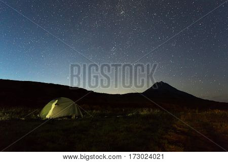 Tourist tent against the night sky and Vilyuchinsky stratovolcano. Brookvalley Spokoyny at the foot of outer north-eastern slope of caldera volcano Gorely.