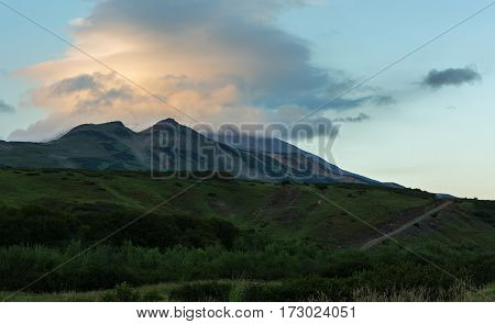 Lenticular clouds above the Vilyuchinsky stratovolcano at dawn. View from the brookvalley Spokoyny at the foot of outer north-eastern slope of caldera volcano Gorely.