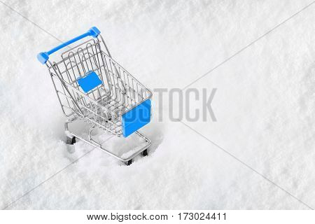 Cart from the grocery store on the snow. Concept of winter shopping. New Year and Christmas buying. Retail trade and advertising. Business ideas.