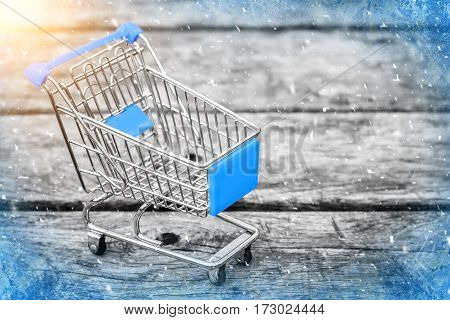 Cart from the grocery store on the old wooden background. Empty shopping trolley. Business ideas and retail trade. Advertising of food products.