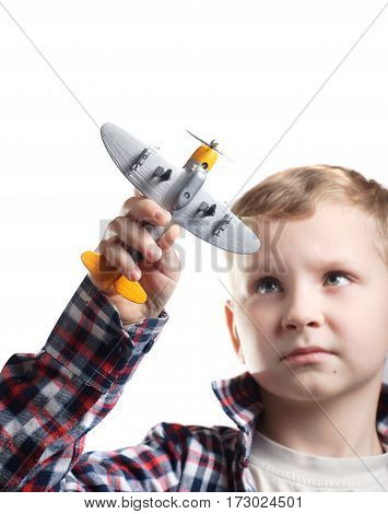 Little boy playing with a model airplane pretending to be a pilot, isolated on a white background, the boy in the shirt, dreams of becoming an airplane pilot,