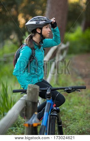 Female biker sitting on fence in countryside forest