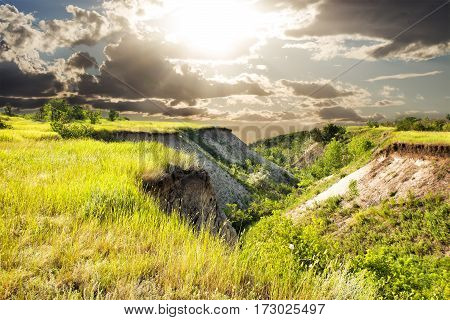 Picturesque green hills at sunset overlooking the dramatic clouds