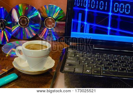 In the foreground a Cup of black coffee to the right of the laptop next to the flash drives rear - drives DVD.
