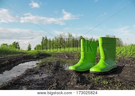 Green rubber boots in the mud next to a puddle on a wet country road. Advertising of footwear. Baby boots. On the background of nature. Close-up view. Agricultural working boots for garden.