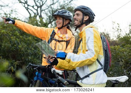 Biker couple with a map pointing in distance at countryside