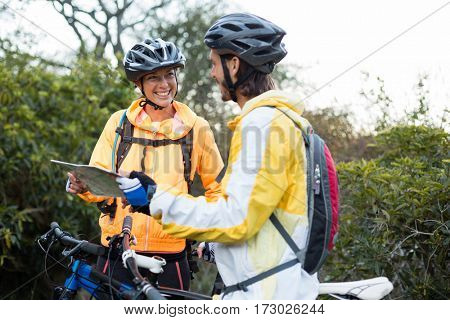 Biker couple interacting over map in countryside