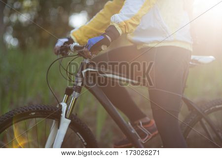 Mid-section of male biker with mountain bike in countryside forest