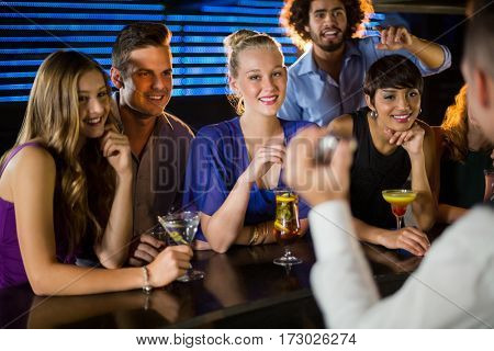 Happy friends standing at counter in bar