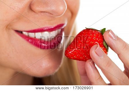 Close up picture of a sexy young woman eating a delicious strawberry