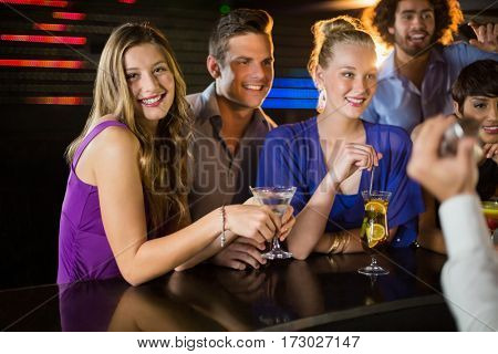 Smiling friends having glass of cocktail at counter in bar