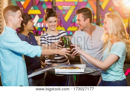 Smiling friends toasting bottle of beer in party at bar