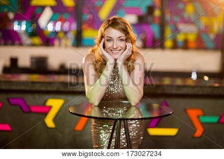Portrait of young woman leaning on table in bar