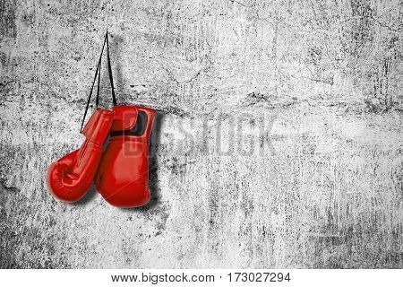 Red boxing gloves on the wall. Concept of sport.