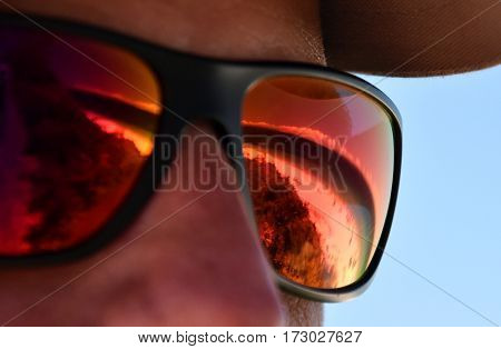 Hyams beach reflected on a red sunglasses. Man in sunglasses with reflective seashore.