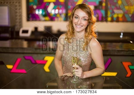 Portrait of young woman holding a glass of champagne in bar