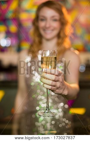 Smiling young woman holding a glass of champagne in bar