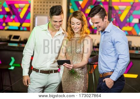 Young woman showing a mobile phone to her friends in bar