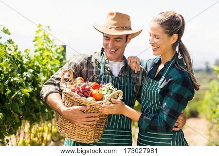 Happy farmer couple holding a basket of vegetables in the vineyard