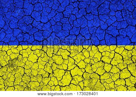Flag of Ukraine painted on cracked wall. Political concept. Old texture. Vintage design. USA flag on cracked earth. Famine and drought. Natural disaster.