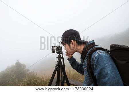 Young photographer with camera on tripod with hazy fog environment in the morning before sunrise