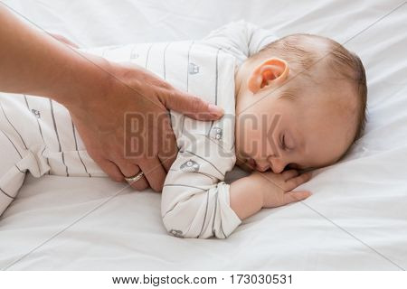 Mom putting baby to sleep in baby bed at home