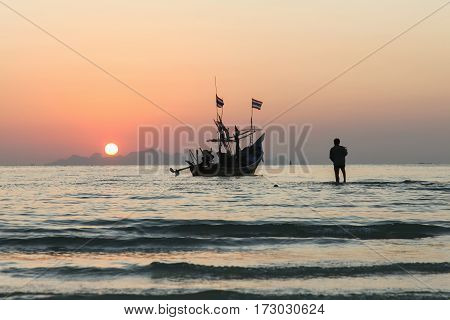 Silhouette of a fisherman walking to the boat at sunset.