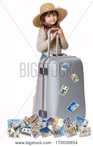 Long haired little girl with straw hat is standing and leaning on a suitcase. Photos of the sights of Venice (Italy) flies around the suitcase. All is on the white background. Vertically.