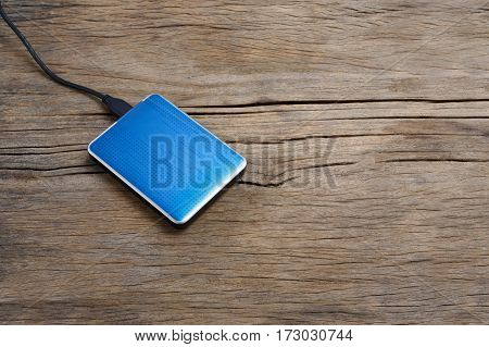External hard drivve with USB post on wooden background