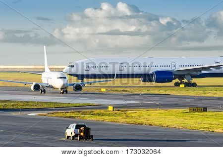 View at the airport with a large aircraft landed, and a small plane departing taxiing for takeoff.