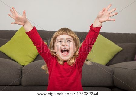 Funny Child With Hands Up And Happy Shouting