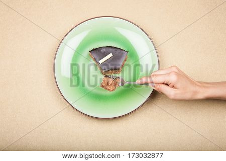 Hand With Fork Taking Piece Of Chocolate Cake On Green Dish