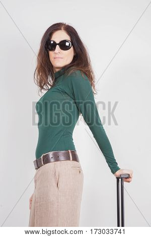 portrait of brown hair adult woman with green sweater beige trousers and sunglasses looking holding suitcase handle isolated on white