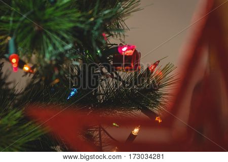 Close-up of fairy light and small gift box hanging on christmas tree