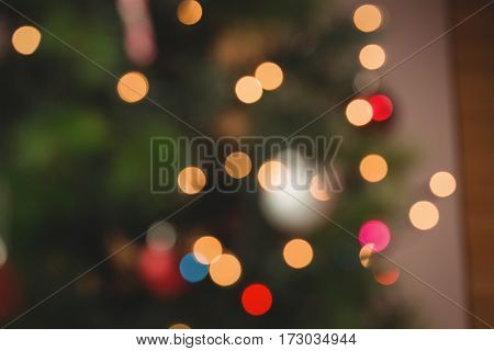 Defocused of christmas tree lights and fireplace at home in the living room