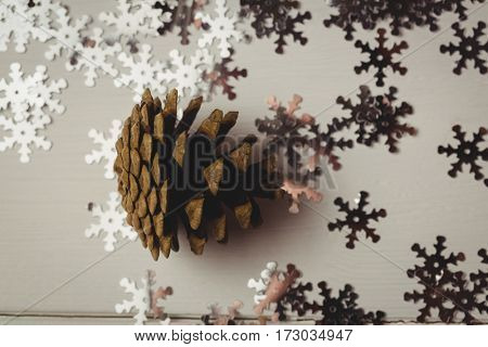 Close-up of pine cone and snowflake on wooden table during christmas time