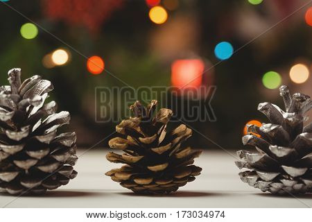 Three pine cones on wooden table during christmas time