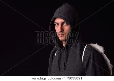 Young Man With Black Hoodie And White Feathered Wings Behind The Back On A Dark Background. Conceptu