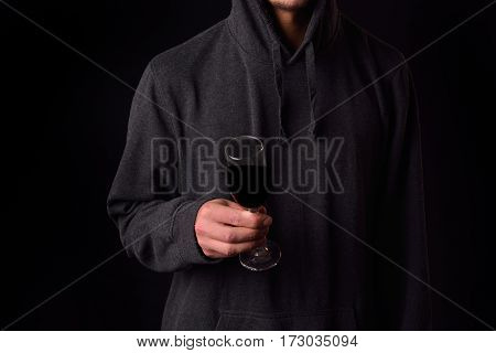Close Up Of The Hand Of A Young Man In A Black Hoodie Holding A Wine Glass On A Dark Background.