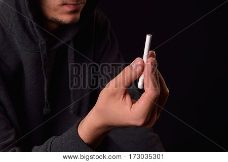 Teenager In A Black Hooded Sweatshirt Holding In His Hand A Cigarette, Is Considering To Ignite It O