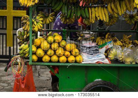 Fruit seller display various kind of exotic tropical fruit like banana and papaya on green cart photo taken in Depok Indonesia java