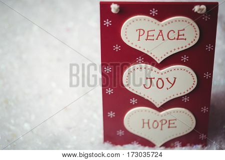 Christmas label with massages of peace, joy and hope on snow