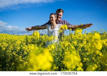 Romantic couple standing with arms outstretched in mustard field on a sunny day