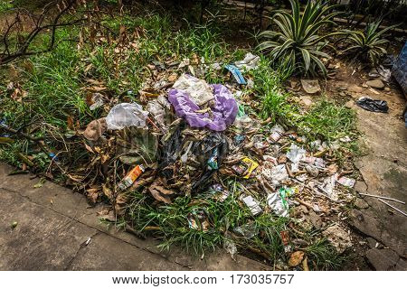 organical and plastic waste heaps littered in a garden with bush and grass photo taken in Depok Indonesia java