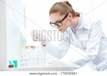 Young concentrated woman scientist in eyeglasses working with test tubes and pipette