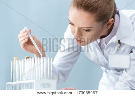 Young concentrated woman scientist working with test tubes and pipette