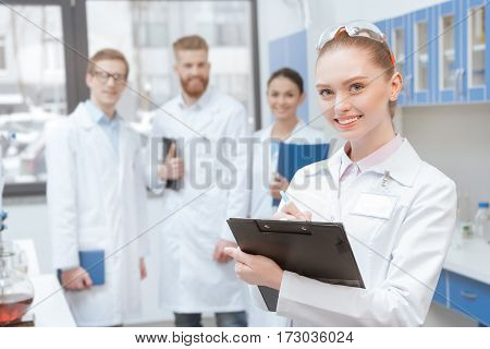 Young smiling woman scientist with clipboard standing near colleagues in lab